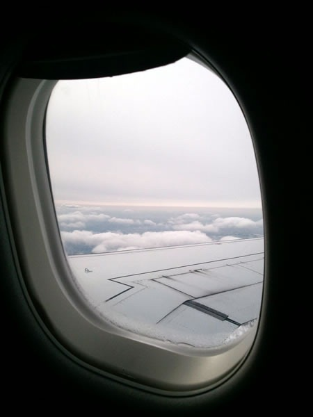 View out of an airplane window, looking at the wing and clouds