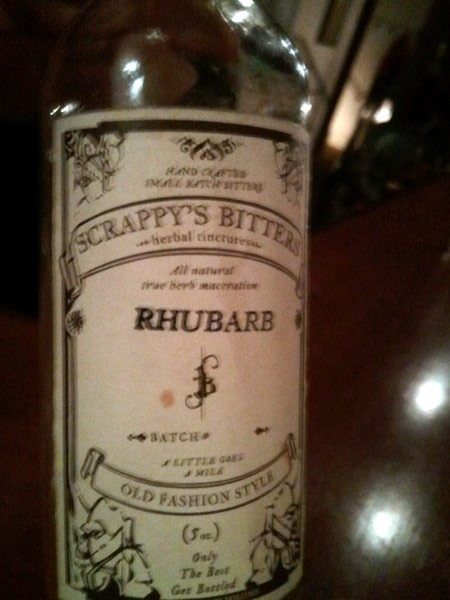 "A bottle of bitters. Label reads ""Scrappy's Bitters / Herbal Tincture / All natural with herb maceration / RHUBARB / Old Fashion Style"""