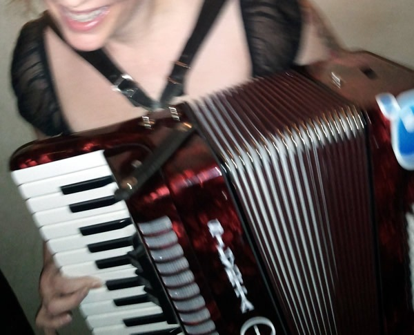 A woman playing Joey deVilla's accordion