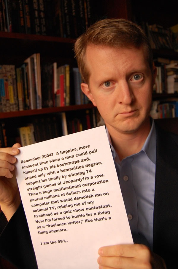 "Ken Jennings holding up a piece of paper that has the following laser printed on it: ""Remember 2004? A happier, more innocent time when a man could pull himself up by his bootstraps and, armed only with a humanities degree, support his family by winning 74 straight games of Jeopardy! in a row. Then a huge multinational corporation poured millions of dollars into a computer that would demolish me on national TV, robbing me of my livelihood as a quiz show contetestant. Now I'm forced to hustle for a living as a 'freelance writer', like that's a thing anymore. I am the 99%."""