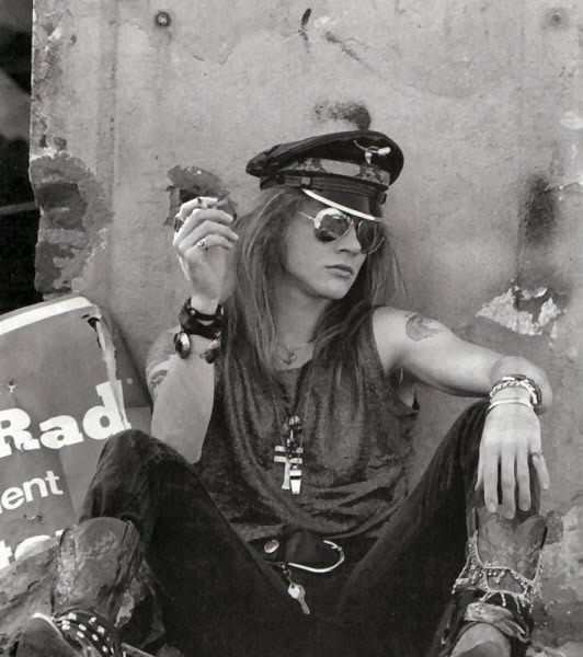 A much skinnier Axl Rose in black jeans and black tank top, sitting on the ground leaning against a wall