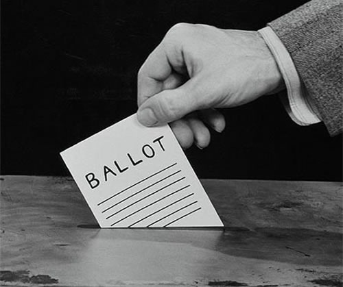 1940s-style photo of a hand putting a ballot into a ballot box