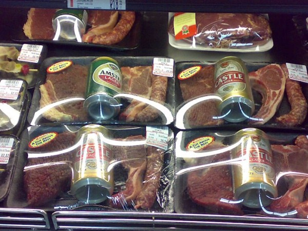 Packaged meat in a grocery store, with a can a beer included.