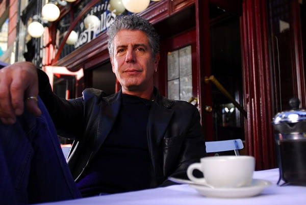 Anthony Bourdain, leaning back at a table at Brasserie Les Halles with a coffee