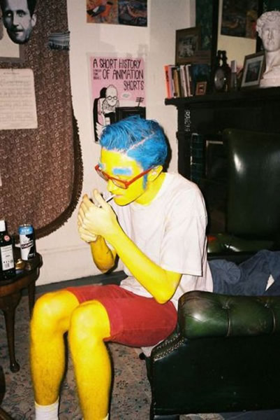 "Guy dressed up as ""Milhouse"" from ""The Simpsons"", in full yellow body paint, with blue hair and blue exaggerated eyebrows, wearing a white t-shirt and shorts, sitting down an lighting a cigarette."