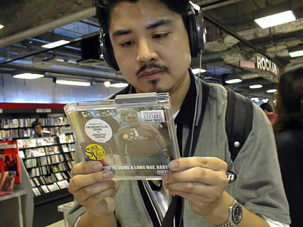 """Joey deVilla wearing headphones in a CD shop, reading the back of Fatboy Slim's """"You've Come a Long Way, Baby"""" CD"""