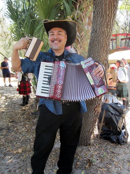 """Joey deVilla in a """"Three Musketeers""""-style hat with feathers, holding a wooden mug with a carved dragon handle, playing the accordion and smiling"""