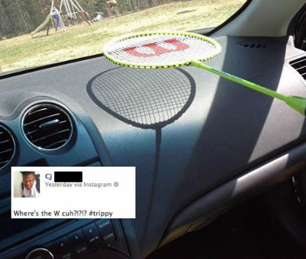 "Badminton racket with a ""W"" painted on the strings, held over a car's dashboard. The badminton strings cast a shadow, but not the ""W"". Inset is a Tweet: ""Where the W, cuh? #Trippy"""