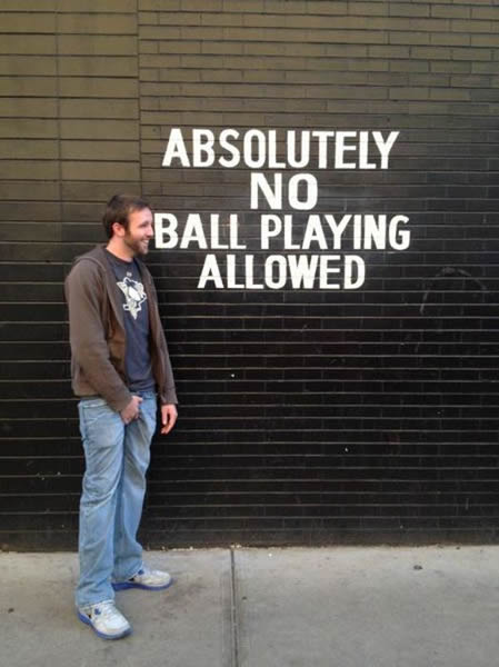"Smiling guy with his hands down his pants in front of a wall with ""Absolutely no ball playing allowed"" painted on it."