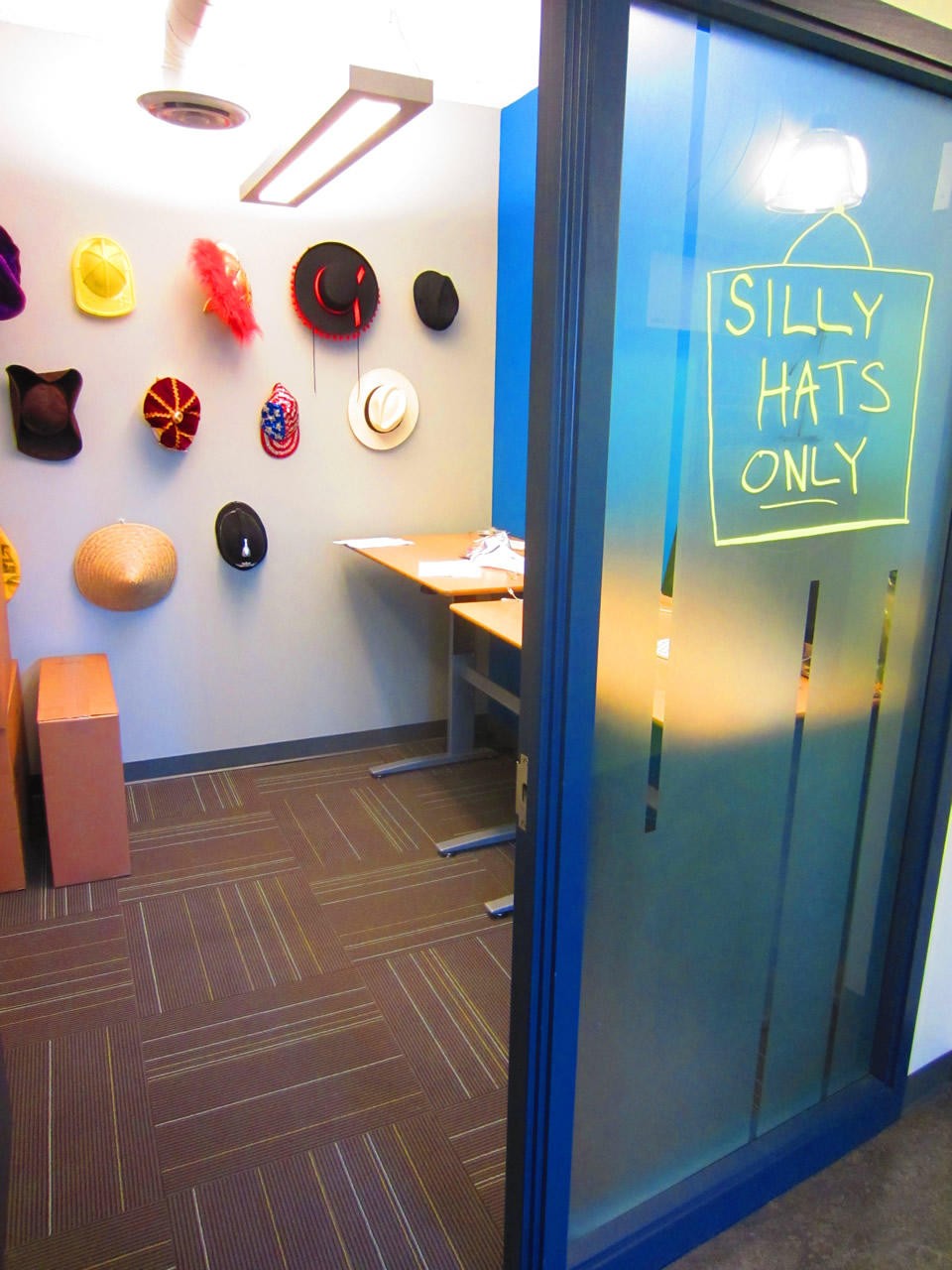 "Shopify's hat room, as seen from outside, with the ""Silly Hats Only!"" sign outside"