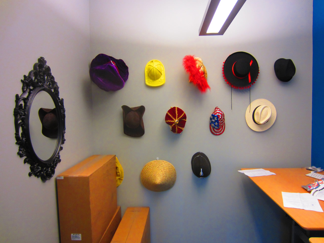 View of hat room, with the hats hanging on the wall and the mirror beside them