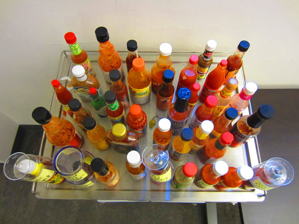 Tabletop packed with various bottles of hot sauce, as seen from above.