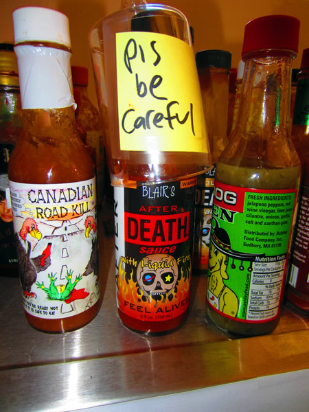 "Close up of bottle of hot sauce, with the label ""Please be careful"""