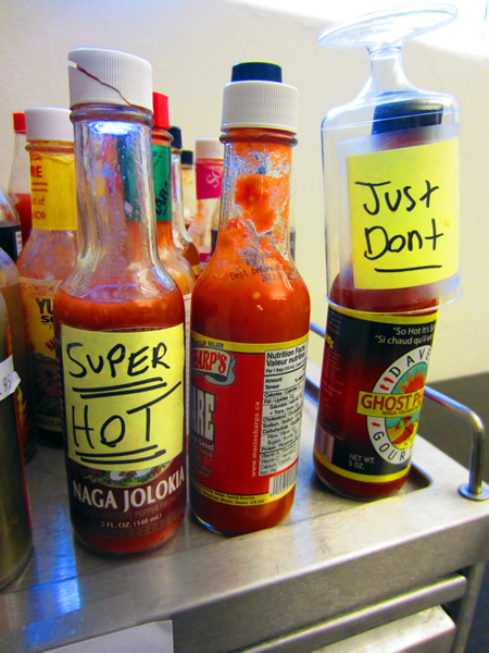 "Close-up of two bottles of hot sauce, one labelled ""Super HOT"" and the other labelled ""Just don't"""