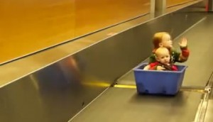 Kids riding in a bin down a luggage conveyor belt