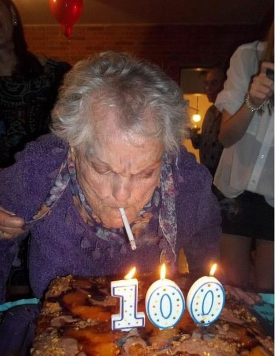 "Old person lighting a cigarette with one of the ""100"" candles on his/her birthday cake"