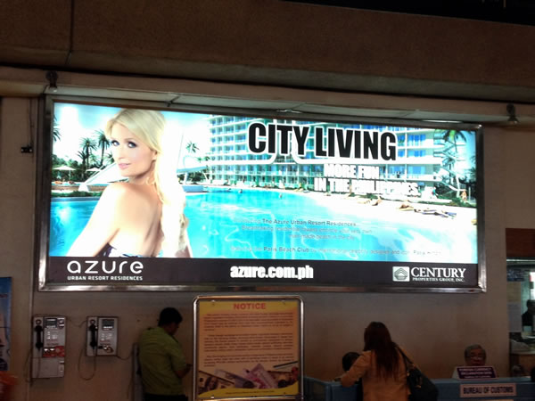 Large billboard ad inside Ninoy Aquino International Airport featuring Paris Hilton promoting a new condo