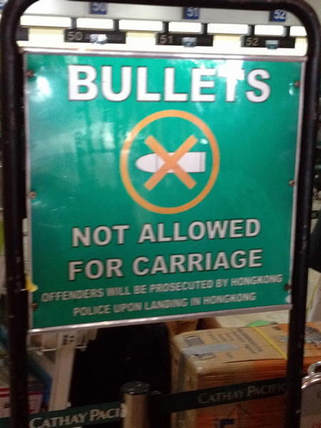"Sign: ""Bullets not allowed for carriage / Offenders will be prosecuted by Hongkong police upon landing in Hongkong"""