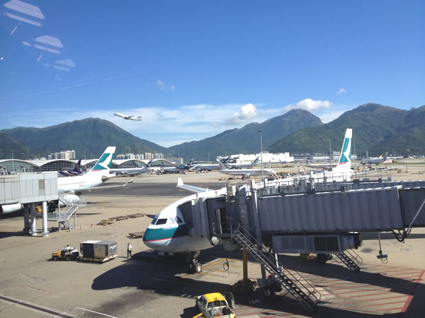 Tarmac at Hong Kong airport, with parked planes in the foreground and mountains and a plane taking off in the background
