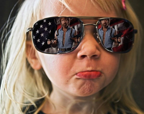 Young girl wearing mirrored sunglasses showing a reflection of Chuck Norris