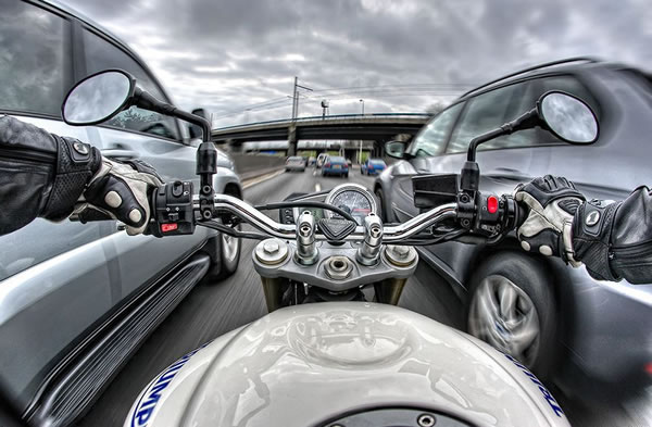 High dynamic range point-of-view shot of a motorbike ride down a busy highway
