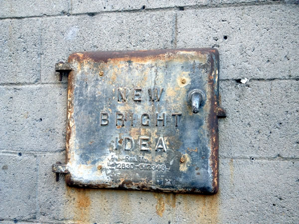 "Metal plate on an exterior wall reading ""New Bright Idea"""