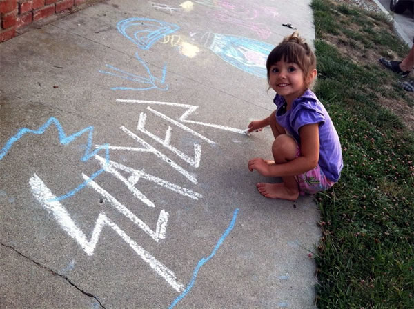 Little girl making a chalk drawing of the Slayer logo on the sidewalk