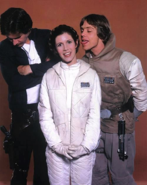 Outtake from a 'Star Wars' promotional photo shoot with Mark Hamill trying to lick Carrie Fisher's ear, as Harrison Ford looks away, embarrassed.