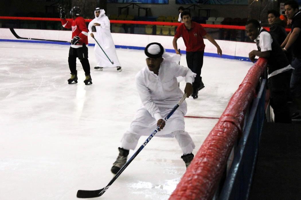 Guys in thawbs playing hockey
