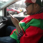 Rannie Turingan in the passenger seat of the C-MAX checking his email on his phone