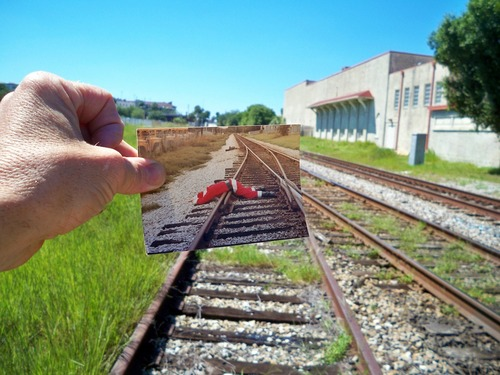 Railroad tracks, with hand holding photo of Santa lying dead across railroad tracks.