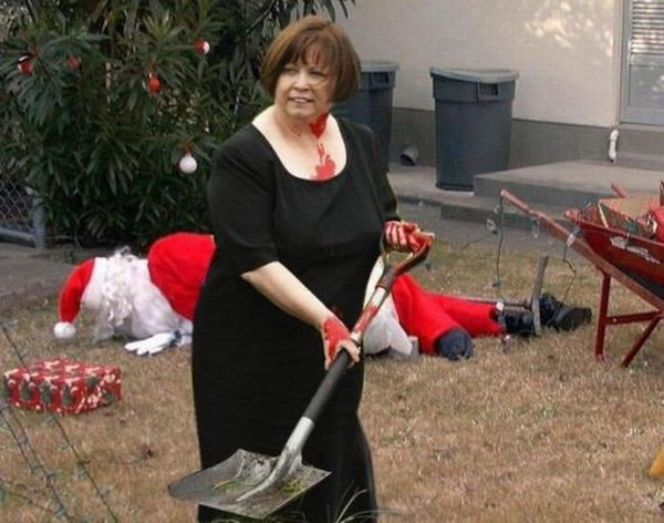 Santa lying face down in the background; blood-covered woman holding shovel in the foreground.