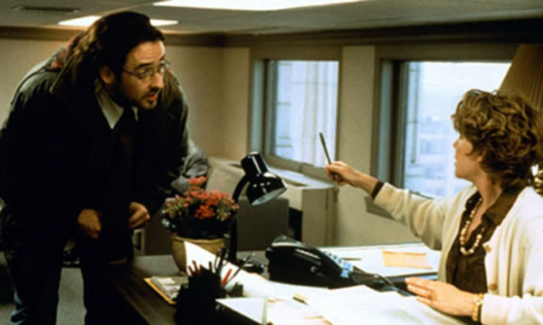 "John Cusack and Caroline Keener in a ""tiny office"" scene from ""Being John Malovich"""