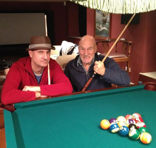 Daniel and Patrick Stewart, posing with cues beside a billiards table