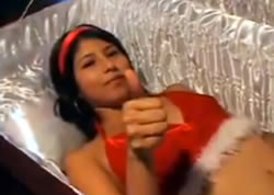 "Sexy model in a Santa bikini, lying in an open coffin, giving the camera a ""thumbs-up"""