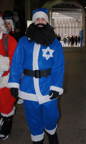 Santa with a blue suit and a Star of David, sporting a thick black beard