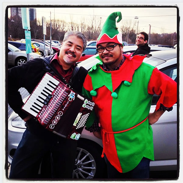 Joey deVilla with his accordion, posing with Rannie Turingan dressed as an elf. In the background, Sean Carruthers looks on.