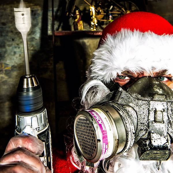 Santa wearing a filter mask and holding a drill, looking menacing