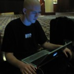 Justin Chapweske zens out with his PowerBook on the hotel lobby carpet.