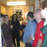 People gathered in a kitchen at a party.