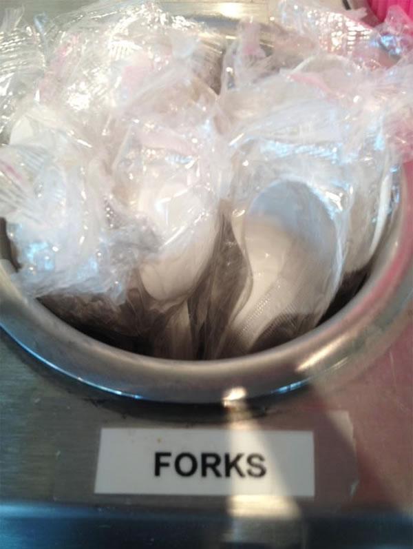 "Spoons in a dispenser labelled ""forks"""
