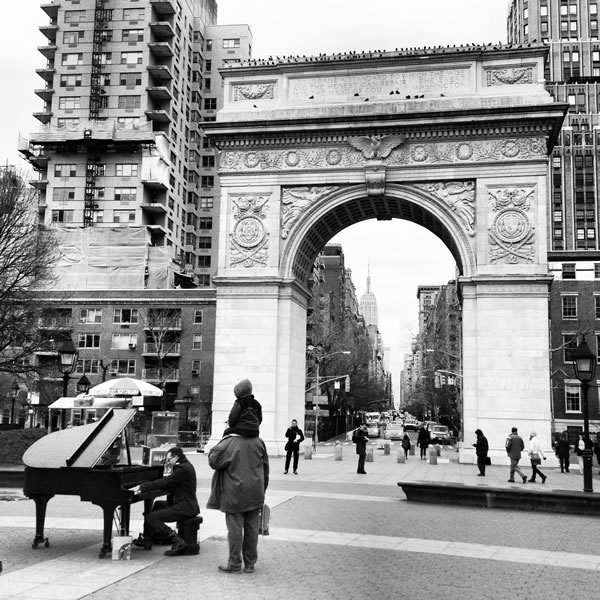 Man playing a grand piano in Washington Square Park as people look on.
