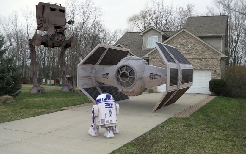 Suburban house with TIE fighter and R2-D2 in the driveway and an AT-AT in the front yard.