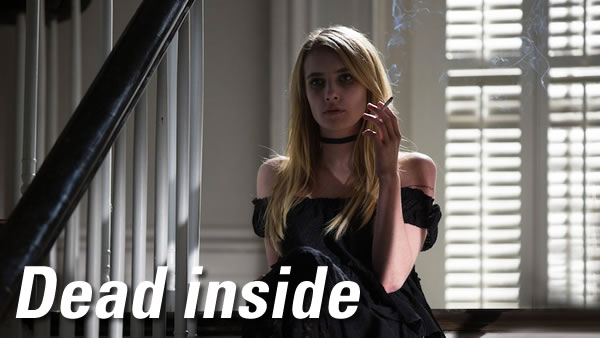 Dead inside: A young blonde woman in a black dress with bare shoulders, sitting at the top of a staircase and smoking a cigarette with a vacant expression on her face.