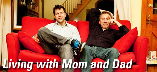 20-something guy sitting on a couch with his 50-something dad.