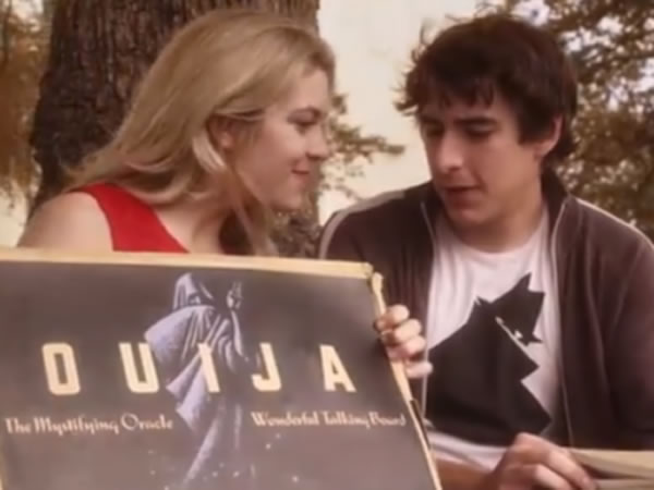 Still from 'Hell No': A cheerleader shows a ouija board to a bookish, sensible-looking guy.