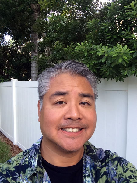 Joey deVilla, in a blue and green aloha shirt, outdoors in Tampa in front of a white fence.