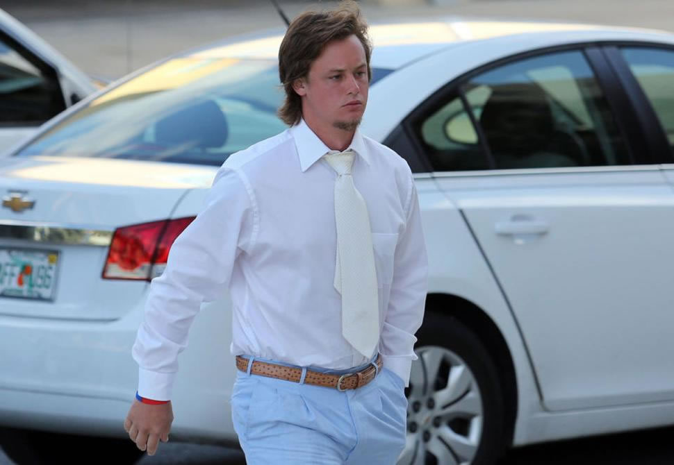 """""""Tayla the Manatee Slaya"""" walks to his court case in a white dress shirt, a '70's era wide white tie, brown golf belt, and baby blue slacks."""