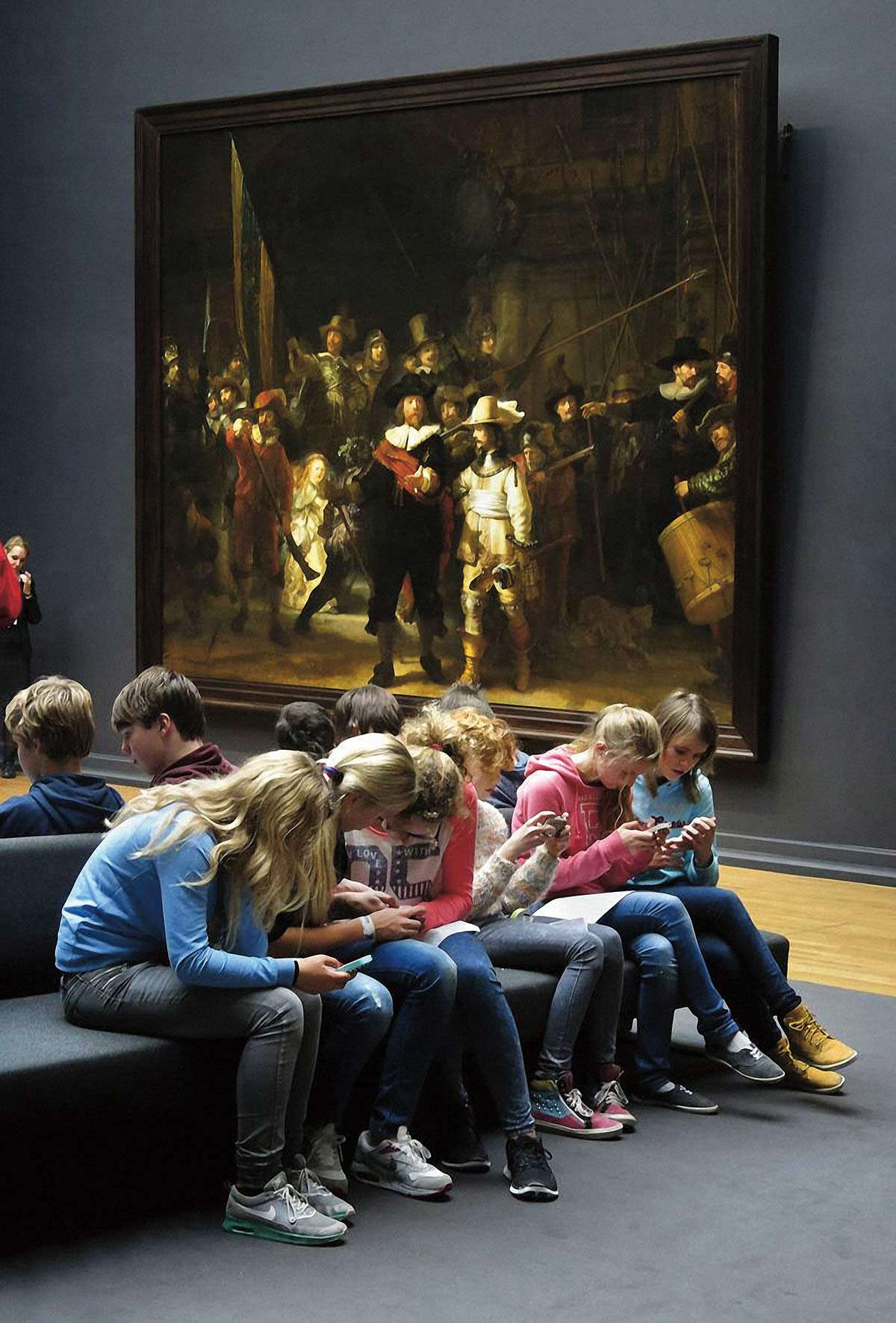 Photo: Schoolchildren sitting on a bench in a museum, engrossed in their smartphones, completely ignoring the large masterpiece hanging on the wall in the background.