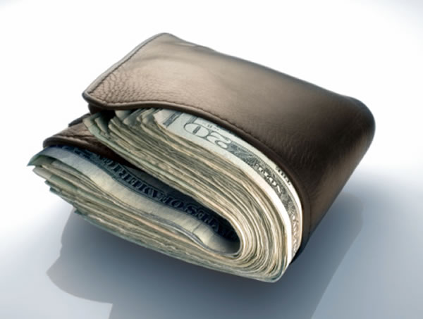Photo: Leather wallet, filled to bursting with US $20 bills.